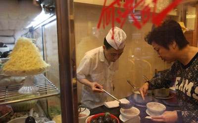 A staff at Ho Hung Kee prepares congee for a customer. —Photo by AFP