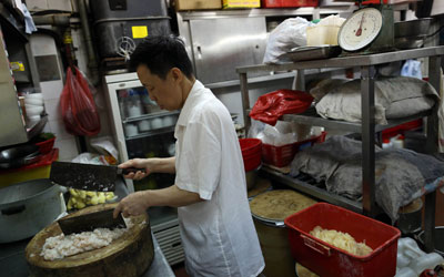 A chef at Ho Hung Kee chopping shrimp with two knives. —Photo by AFP