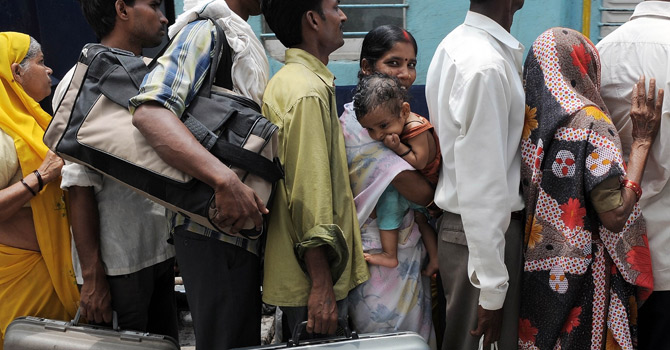 an Indian woman carries a child as she queues for an overcrowded train at a railway station in New Delhi.