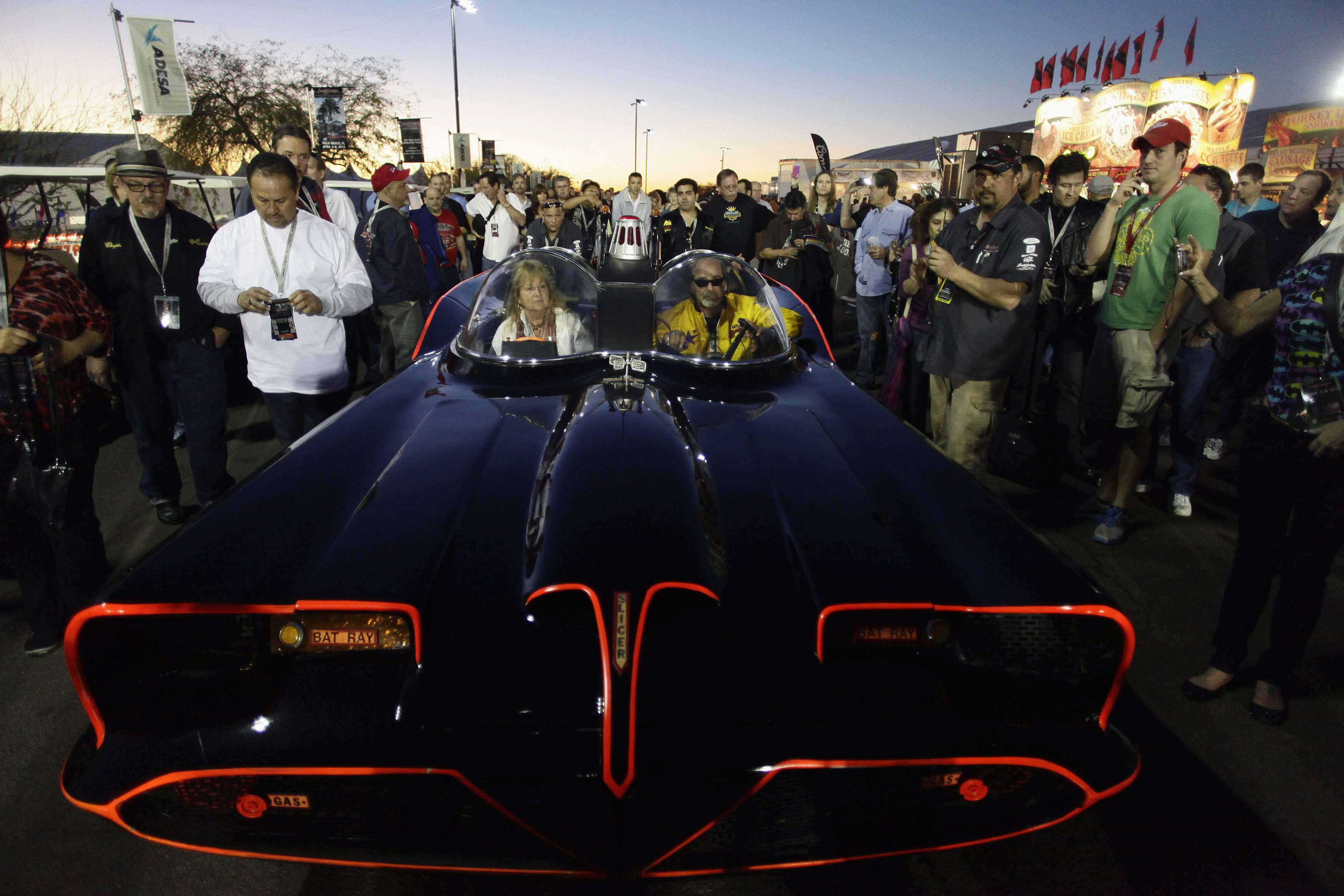 People surround the original Batmobile during the Barrett-Jackson collectors car auction in Scottsdale, Arizona January 19, 2013. The vehicle was sold for $4,200,000, according to the auction company. REUTERS/Joshua Lott (UNITED STATES - Tags: ENTERTAINMENT SOCIETY BUSINESS TRANSPORT)