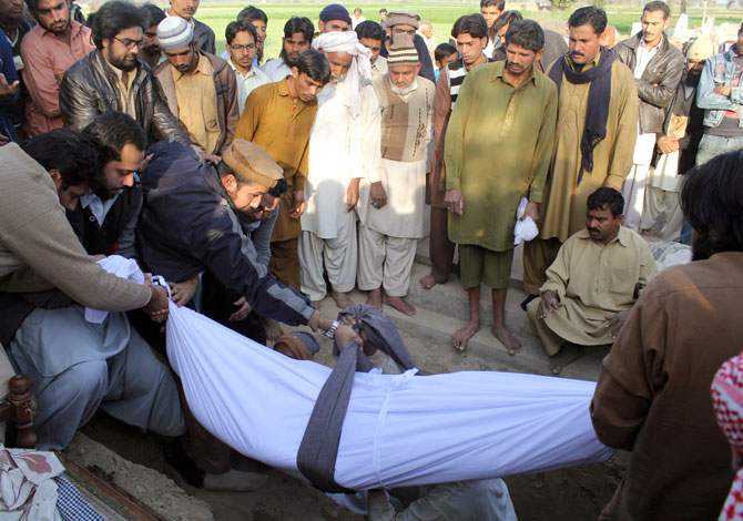 Relatives bury the mortal remains of Kamran Faisal, who was investigating a corruption scandal involving Prime Minister Raja Pervez Ashraf and was found dead in a government hostel, in Mian Channu on January 19, 2013. - Photo by AFP