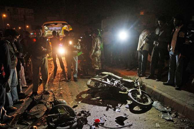 A Pakistani police officer, left, talks on the radio while cameramen flim the site of a blast in Karachi, Pakistan, Tuesday, Jan. 1, 2013. - Photo by AP