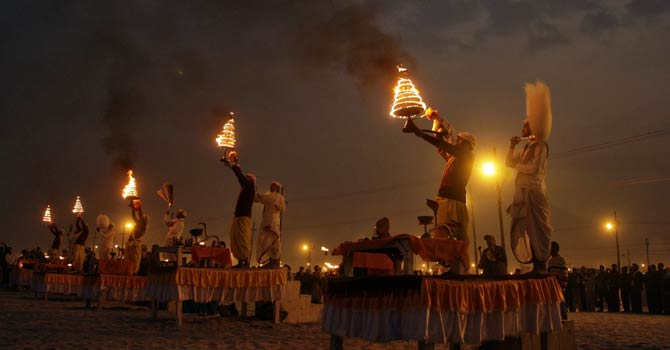"Hindu priests hold oil lamps as they perform evening prayers on the banks of river Ganges during the ""Kumbh Mela"", or Pitcher Festival, in the northern Indian city of Allahabad Jan 17, 2013. During the festival, hundreds of thousands of Hindus take part in a religious gathering at the banks of the river Ganges. ""Kumbh Mela"" will again return to Allahabad in 12 years. - Reuters"