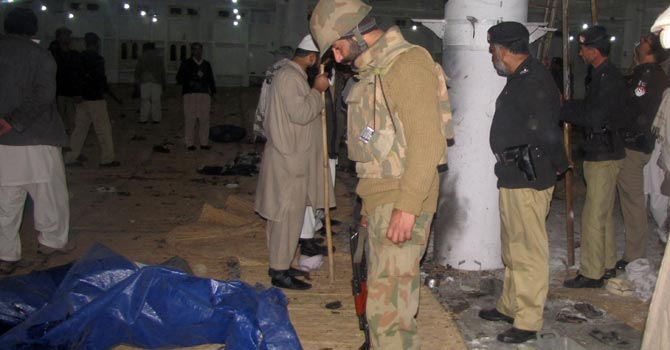 Security officials inspect the debris following a blast inside a religious seminary in Mingora. – Photo by AFP