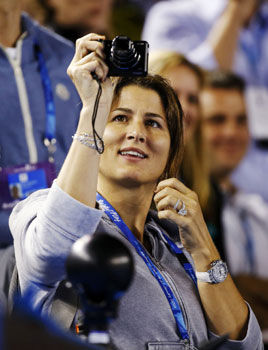 Mirka Federer, wife of Roger Federer of Switzerland, takes pictures with her camera during his men's singles match against Bernard Tomic of Australia. -Photo by Reuters