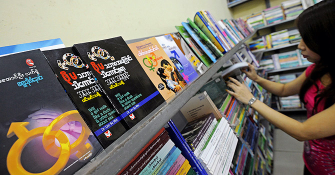 "This picture taken on January 5, 2013 shows a woman browsing in a book shop where Myanmar sex education books are on display in Yangon. With its glossy pages of pouting models and racy romance tips, Myanmar's first sex education magazine has got the usually demure nation hot under the collar as it cashes in on new-found cultural freedom. ""Hyno"" has sparked fevered debate since hitting Myanmar's bookstores in November, where it has become a must-read among the young and curious, just a few months after the end of direct censorship in the former junta-ruled nation. AFP PHOTO / Soe Than WIN"