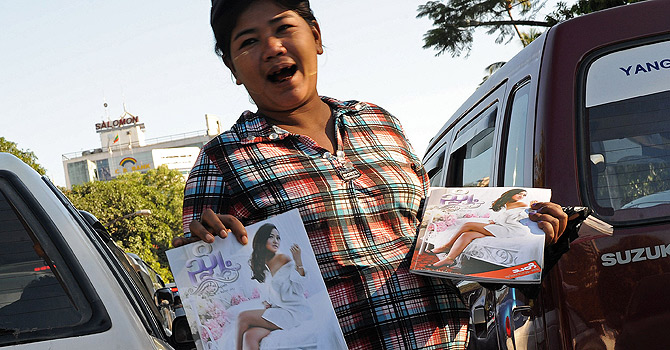 "This picture taken on December 20, 2012 shows a Myanmar woman selling Myanmar's first sex education magazine in downtown Yangon. With its glossy pages of pouting models and racy romance tips, Myanmar's first sex education magazine has got the usually demure nation hot under the collar as it cashes in on new-found cultural freedom. ""Hyno"" has sparked fevered debate since hitting Myanmar's bookstores in November, where it has become a must-read among the young and curious, just a few months after the end of direct censorship in the former junta-ruled nation. AFP PHOTO/ Soe Than WIN"