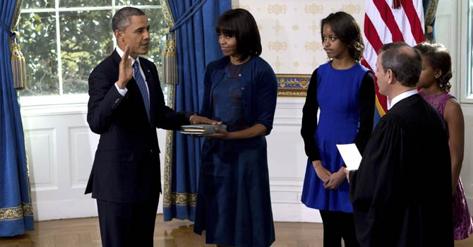 President Barack Obama is officially sworn-in by Chief Justice John Roberts, not pictured, in the Blue Room of the White House during the 57th Presidential Inauguration in Washington, Sunday Jan. 20, 2013, as first lady Michelle Obama, holds the Robinson Family Bible, as daughter Malia and Sasha watch.  - AP Photo