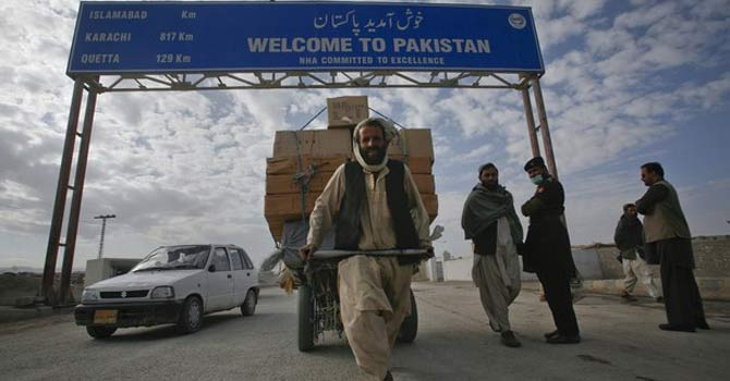 A Pashtun man passes a road sign while pulling supplies towards the Pakistan-Afghanistan border crossing. – File photo by Reuters