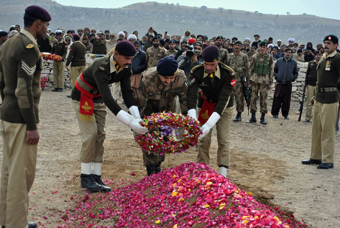 This photograph taken on January 8, 2013, shows Pakistani army officials laying a wreath on the grave of soldier Mohammad Aslam.