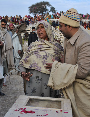 In this photograph taken on January 8, 2013, a mourner comforts the mother of Pakistani soldier Mohammad Aslam.