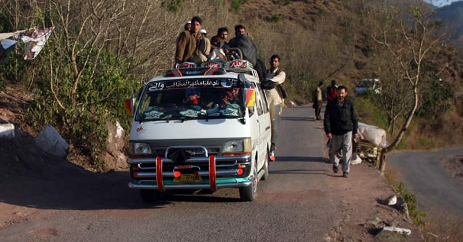 Pakistani Kashmiris ride a van heading towards the town of Titrinot, some 30 kilometers north of Battal sector close of Pakistan-India border. – Photo by AFP