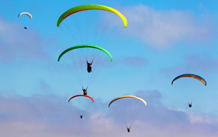 Sport fanatics having a taste of paragliding over the Pacific Ocean. ?Photo by AP