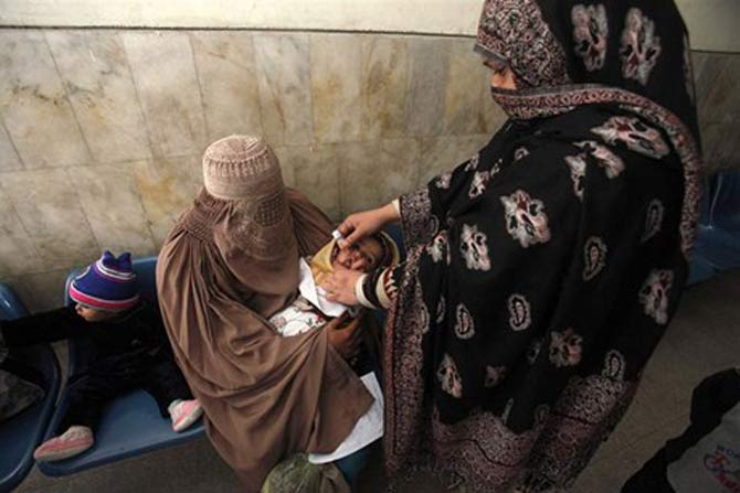 A lady health worker administers polio drops in Peshawar. – File photo by Reuters