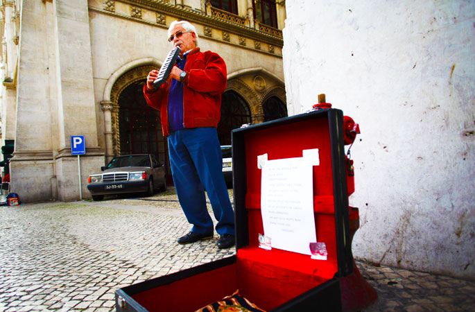 Jose Fonseca, 62, who has been unemployed for six months, plays music on the street for money in downtown Lisbon, Portugal. Fonseca, who has been working in the construction sector for 43 years, says he receives 274 euro ($358.5) as a monthly unemployment benefit. -Photo by AP