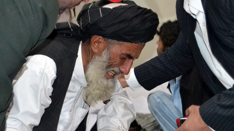 Pakistani men comfort an elderly mourner grieving over the death of a relative at a hospital following the bomb explosion.