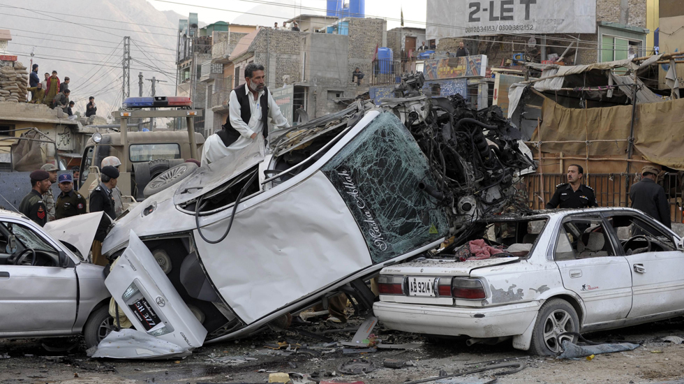 Pakistani security personnel search the wreckage of vehicles after the bomb explosion.