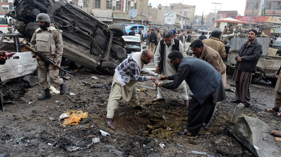 Pakistani security personnel examine the site of the bomb explosion.
