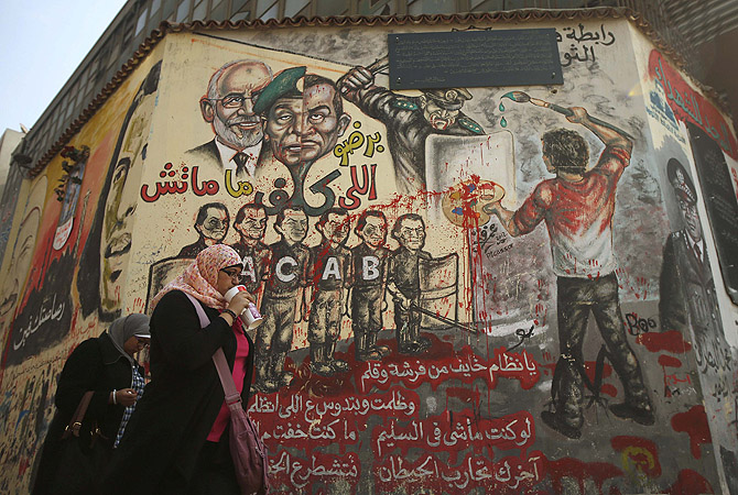 Egyptians walk past graffiti on a wall at Tahrir Square in Cairo.?Photo by Reuters