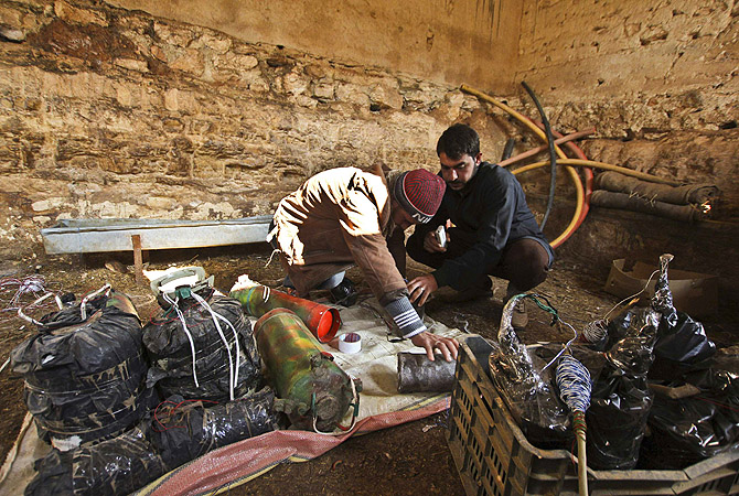 Syrian brothers who used to be musicians make homemade explosives for the Free Syrian Army in the Ma'ar Shamarine village near Idlib.?Photo by Reuters