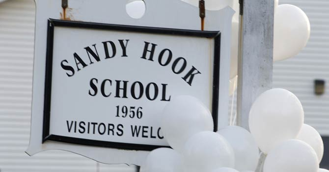 Balloons hang on a sign at the entrance to Sandy Hook School in this Dec 15, 2012 photo in Newtown, Connecticut.   Students at the elementary school where a gunman massacred 26 children and teachers last month were returning to class for the first time Jan 3, 2012 in a new building adapted to look exactly like their old one. - AFP Photo