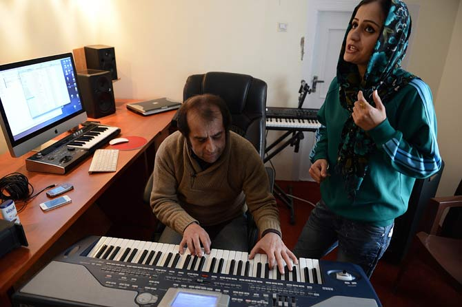 Soosan Feroz, 23, (R) Afghanistan's first female rap musician, practices with Afghan pop musician Farid Rastagar at a recording studio in Kabul. – Photo by AFP