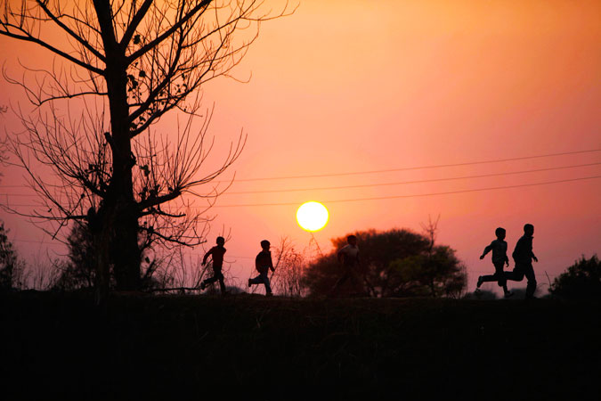 Indian children run near the India-Pakistan international border fencing at Suchet Garh, south of Jammu, in India. Despite the worst bout of violence in years along the disputed Kashmir border, Pakistani and Indian officials have kept tension from spiralling out of control. ?Photo by AP