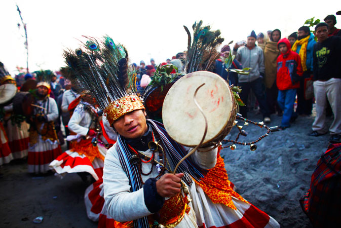 Nepalese witch doctors wearing traditional ornaments made of bones, dance as devotees take holy dip in Narayani river during Maghe Sankranti at Devghat, in Nepal. Maghe Sankranti is a Nepalese festival observed on the first day of the Hindu calendar month of Magh. On this day, the sun is believed to travel northwards to Makar Rashi (Capricorn). Hindus take ritual baths during this festival, notably at auspicious river locations. ?Photo by AP