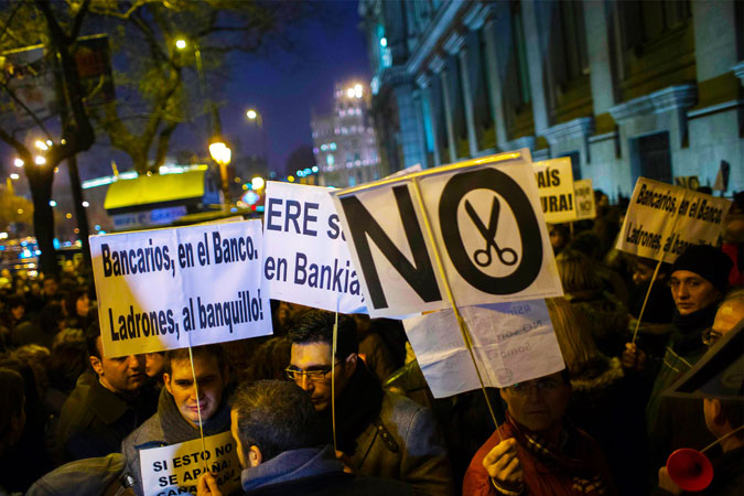 Bankia workers protest against jobs cuts outside the Bank of Spain building in Madrid. The placard (L) reads: ?Bank workers to the bank, thieves to the courtroom dock?. -Photo by Reuters