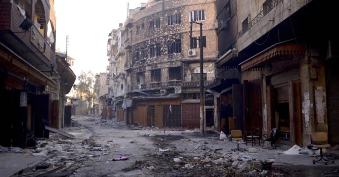 A view shows damaged buildings and an erected Syrian flag in the old city of Aleppo Jan 3, 2013. - Reuters