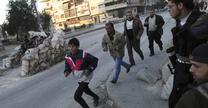 Residents run to take cover as Free Syrian Army fighters take their position behind sandbags during clashes with forces loyal to Syria's President Bashar al-Assad in Aleppo's Bustan al-Qasr district in this Dec 30, 2012 file photo. - Reuters