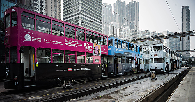 In this picture taken on January 11, 2013 a worker (R) enters a tram at the Whitty street depot, the main terminus stop of the Hong Kong Tramway Ltd, in Hong Kong. Trundling along slowly against a backdrop of glittering skyscrapers, Hong Kong's trams are entering a new phase of their life but their well-loved retro look is here to stay.  AFP PHOTO / Philippe Lopez