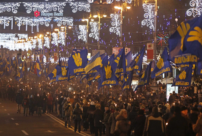 "Activists of the Svoboda (Freedom) Ukrainian nationalist party hold torches as they take part in a rally to mark the 104th year since the birth of Stepan Bandera, one of the founders of the Organization of Ukrainian Nationalists (OUN), in Kiev. The words on the flags read, ""Freedom"".—Photo by Reuters"