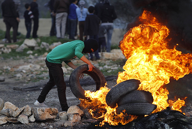 A stone-throwing Palestinian protester burns a tyre during clashes with Israeli security forces (unseen) at a protest against the nearby Jewish settlement of Kdumim, in the West Bank village of Kfar Kadum, near Nablus.—Photo by Reuters