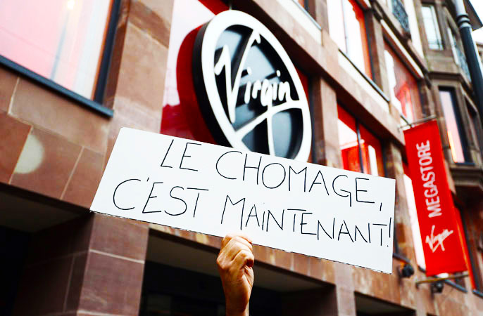 A Virgin Megastore employee holds a sign reading ?Unemployment, it's now? during a demonstration against planned job cuts at the entrance of the store in Strasbourg, eastern France. -Photo by AFP