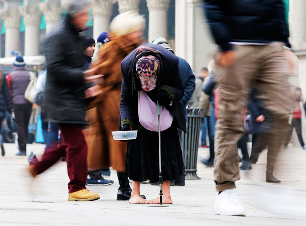 A woman begs for money amid passers-by in downtown Milan, Italy. -Photo by AP