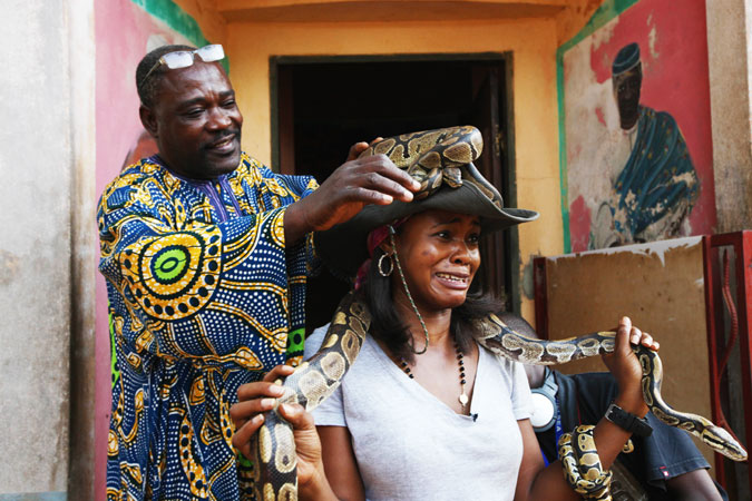 Aduare Achumba, a visitor to the Temple of Pythons, reacts as a guide puts a python on her head.