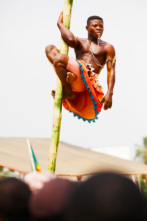 People watch as a Voodoo worshipper performs.