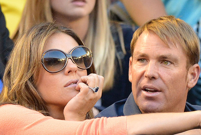 Former Australian cricketer Shane Warne (R) and British actress Elizabeth Hurley speak as Switzerland's Roger Federer plays during his men's singles match against Australia's Bernard Tomic. -Photo by AFP