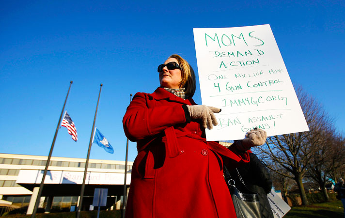 A mother protests against organisers of the East Coast Fine Arms Show to cancel its event out of respect for the still grieving community of Newtown, Connecticut. -Photo by Reuters