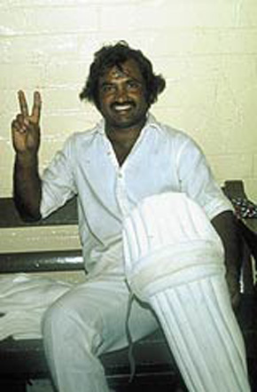 Mushtaq flashes a 'V' sign in the dressing room after cracking a century at the Port of Spain.