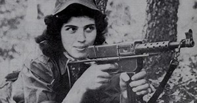 A female fighter of the FLN posing with her gun during the Algerian War of Independence against the French.