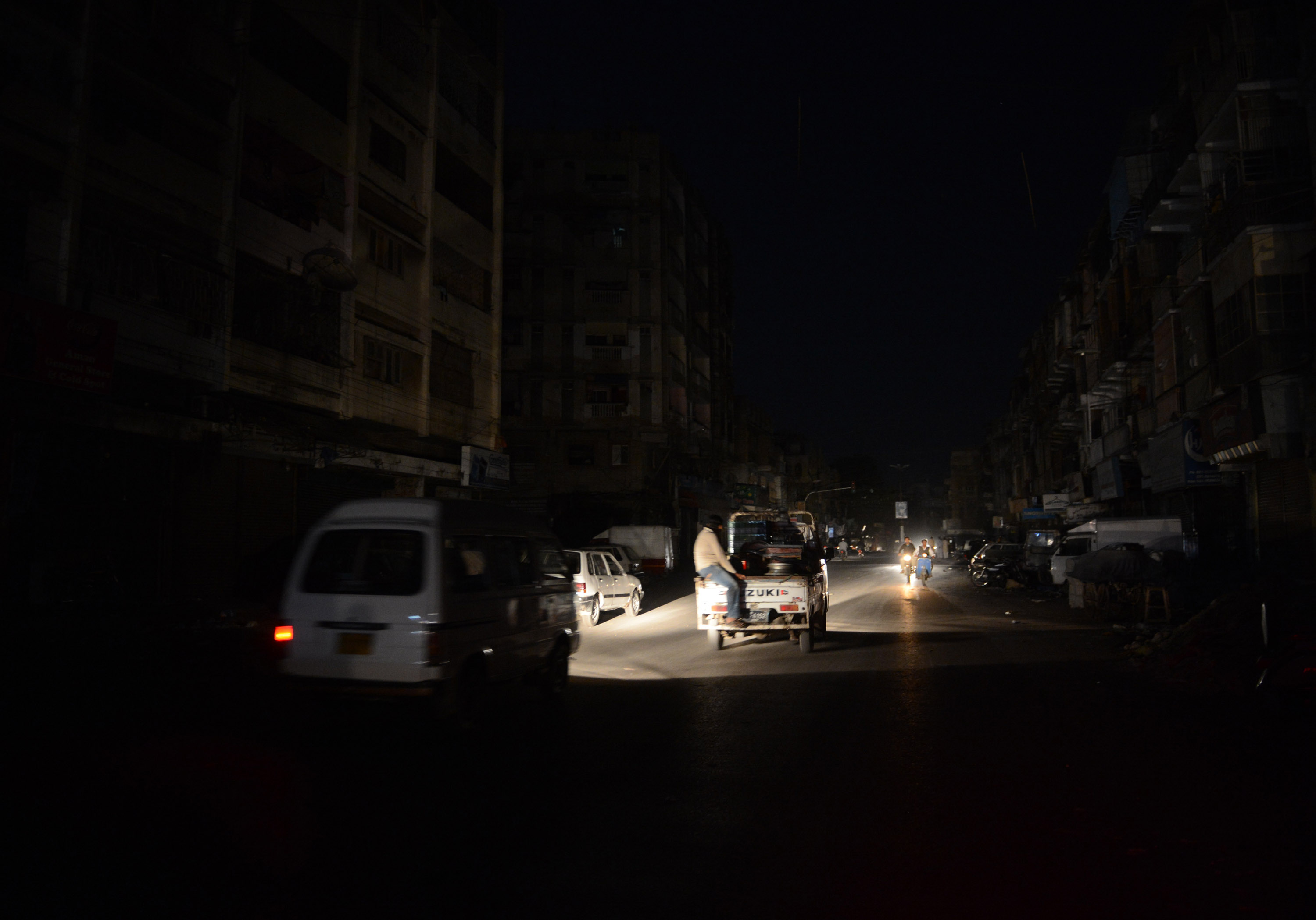 This picture taken on February 24, 2013 shows Pakistani commuters driving on a street in a residential area during a nationwide power blackout in Karachi.  Pakistan was hit by a nationwide blackout for more than two hours after the breakdown of a major plant caused power stations to stop working across the country, officials said on February 25.  AFP PHOTO/Asif HASSAN