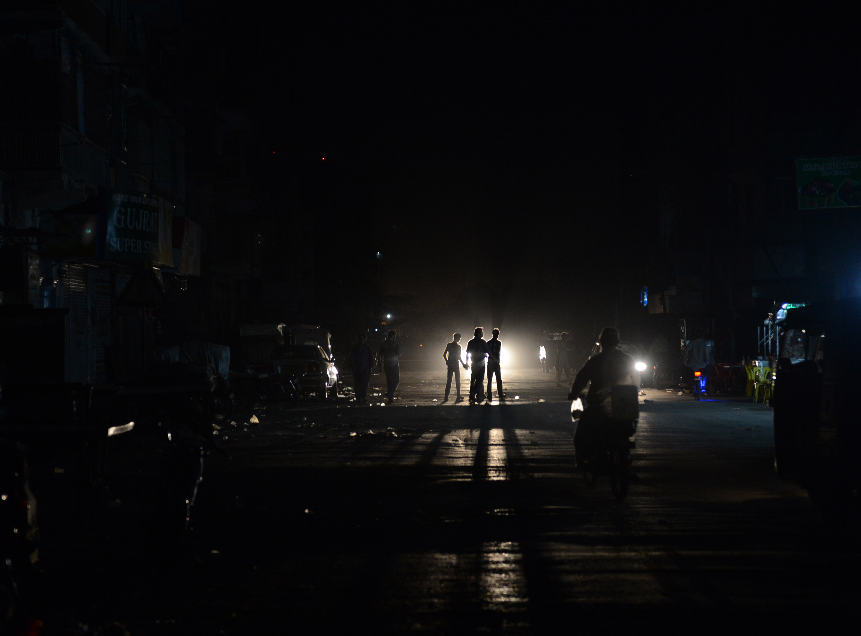 This picture taken on February 24, 2013 shows Pakistani youth crossing a street during a nationwide power blackout in Karachi.  Pakistan was hit by a nationwide blackout for more than two hours after the breakdown of a major plant caused power stations to stop working across the country, officials said on February 25.  ? AFP Photo