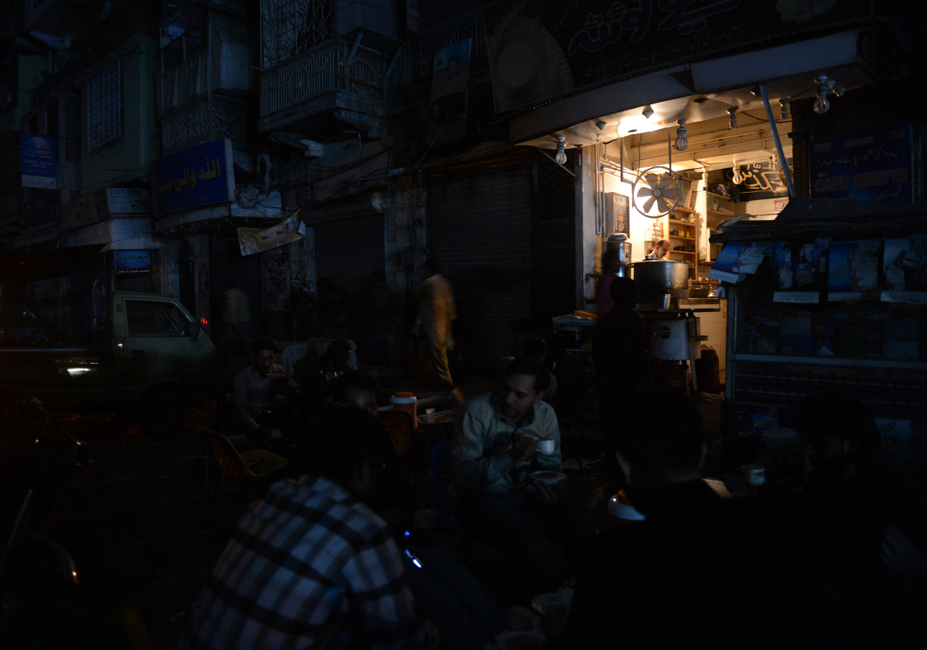 This picture taken on February 24, 2013 shows Pakistani people drinking tea outside a restaurant during a nationwide power blackout in Karachi.  Pakistan was hit by a nationwide blackout for more than two hours after the breakdown of a major plant caused power stations to stop working across the country, officials said on February 25.  AFP PHOTO/Asif HASSAN