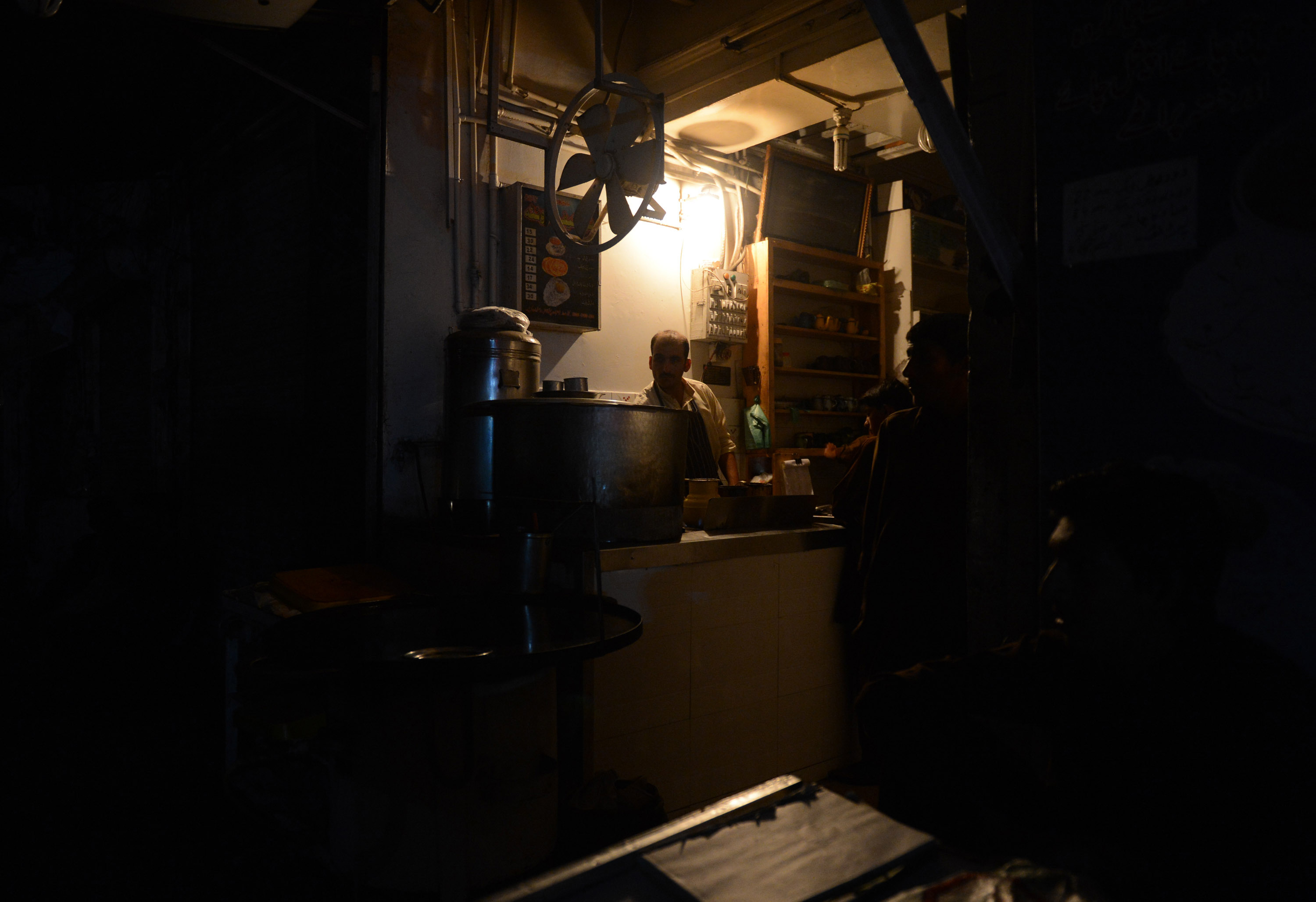 This picture taken on February 24, 2013 shows Pakistani man preparing tea at his restaurant during a nationwide power blackout in Karachi. Pakistan was hit by a nationwide blackout for more than two hours after the breakdown of a major plant caused power stations to stop working across the country, officials said on February 25.  ? AFP Photo