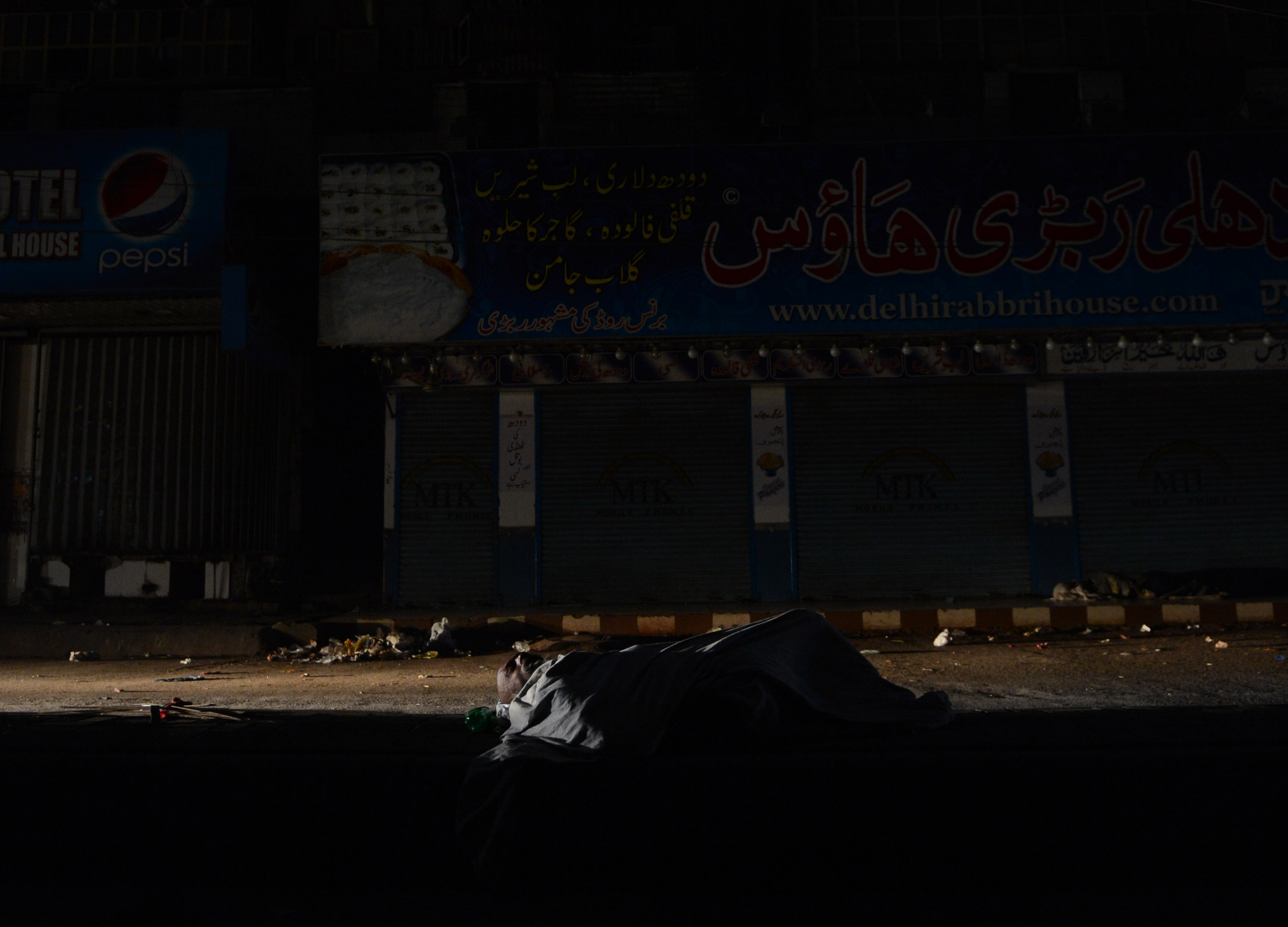 This picture taken on February 24, 2013 shows a homeless Pakistani man sleeping on a roadside during a nationwide power blackout in Karachi. Pakistan was hit by a nationwide blackout for more than two hours after the breakdown of a major plant caused power stations to stop working across the country, officials said on February 25.  AFP PHOTO/Asif HASSAN