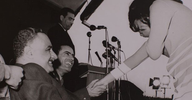 A young Libyan college student blushes after shaking hands with the then 29-year-old Qadhafi in 1970. Also seen in the picture is Egyptian leader, Abdel Nasser, who was on a visit to Libya.