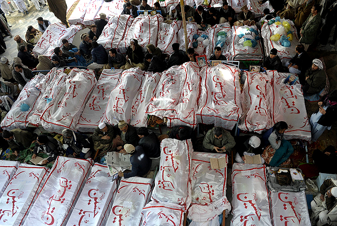 Pakistani Shia Muslims gather around the coffins of bomb attack victims as they demonstrate in Quetta on February 18, 2013. ? AFP Photo