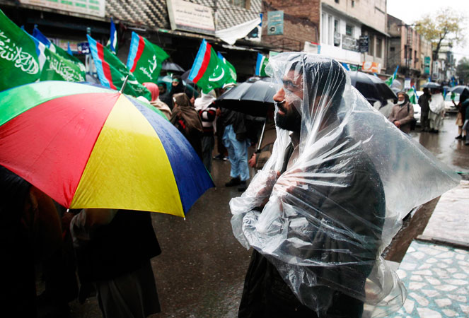 A supporter of Jamaat-i-Islami (JI) uses a plastic sheet to take shelter from the rain as he takes part in a rally marking Kashmir Solidarity Day in Peshawar.